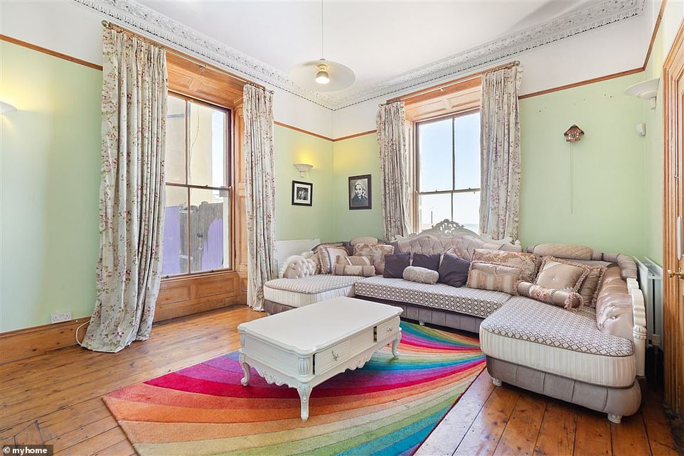 So much colour! Another of the home's reception rooms has an extra pop of colour in the form of a rainbow rug, as well as an Edwardian-style sofa