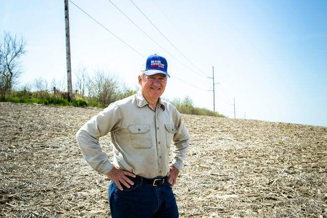 Jim Dane poses for a photo in a bean field, Tuesday, April 27, 2021, near his home off of Dane Road Southwest in Johnson County, Iowa. The power lines behind him were constructed in the 1980s and lead into Iowa City.