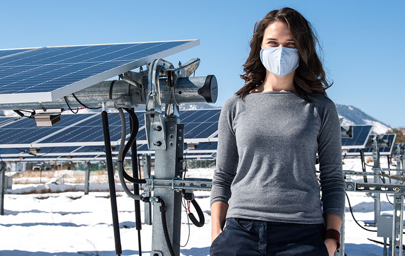 A woman stands next to a PV array at NREL.