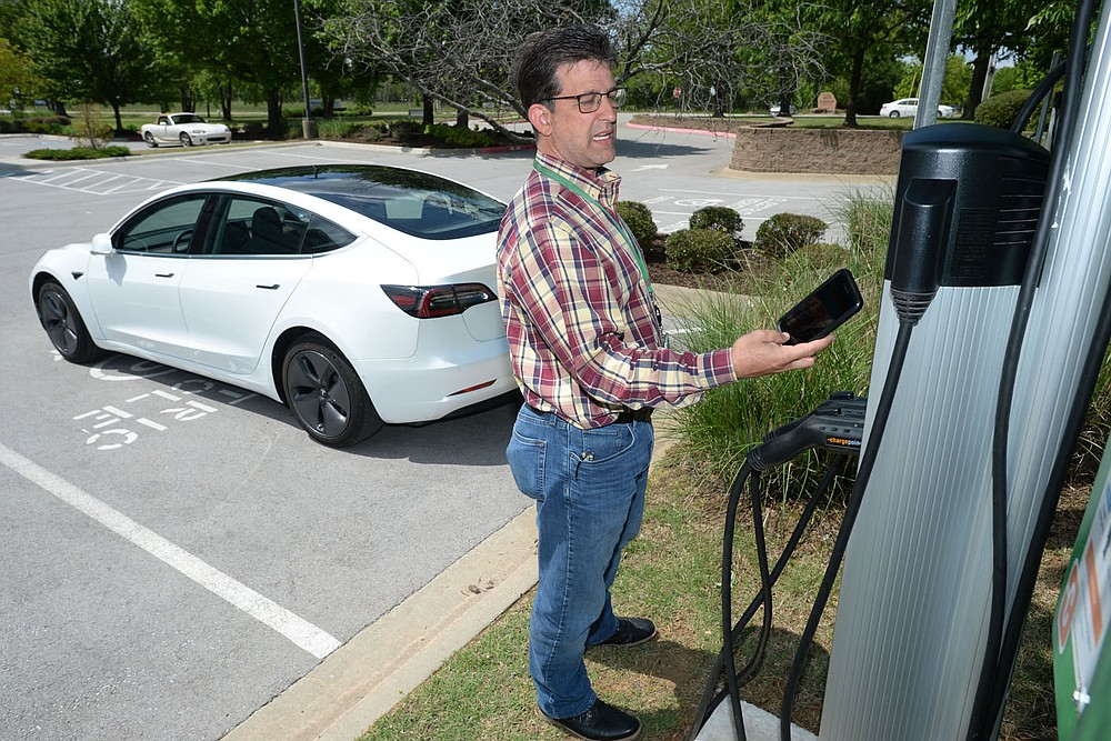 Kris Williams, director of energy services for Ozarks Electric Cooperative Corp. demonstrates how one of the cooperative‰Ûªs Tesla Model 3 electric vehicles is charged Wednesday, May 12, 2021, at the cooperative‰Ûªs offices in Fayetteville. It can be challenging to find charging stations for electric vehicles in rural areas of Arkansas, but both the state and private companies are working to change that. Visit nwaonline.com/210518Daily/ for today's photo gallery.  (NWA Democrat-Gazette/Andy Shupe)