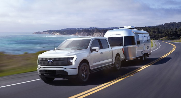 A silver 2022 Ford F-150 Lightning Lariat, an electric pickup truck, shown towing a camping trailer on a coastal road.