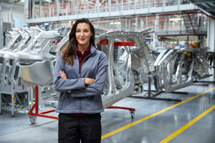 An engineer in front of an auto assembly line.