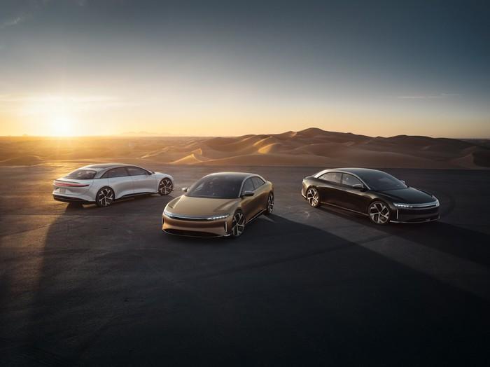 Various trims of the Lucid Air luxury sedan in the desert at sunrise.