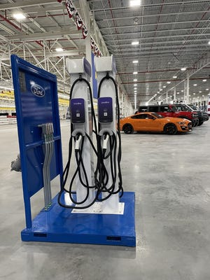 An electric vehicle charging station and Ford vehicles are displayed inside the automaker's Rouge Electric Vehicle Center for President Joe Biden's visit Tuesday, May 18, 2021.