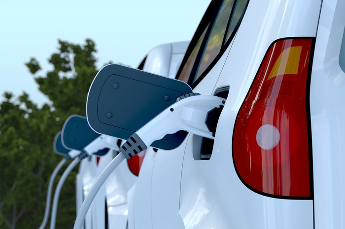 Three electric vehicles sit in a row as their electric plugs are inserted