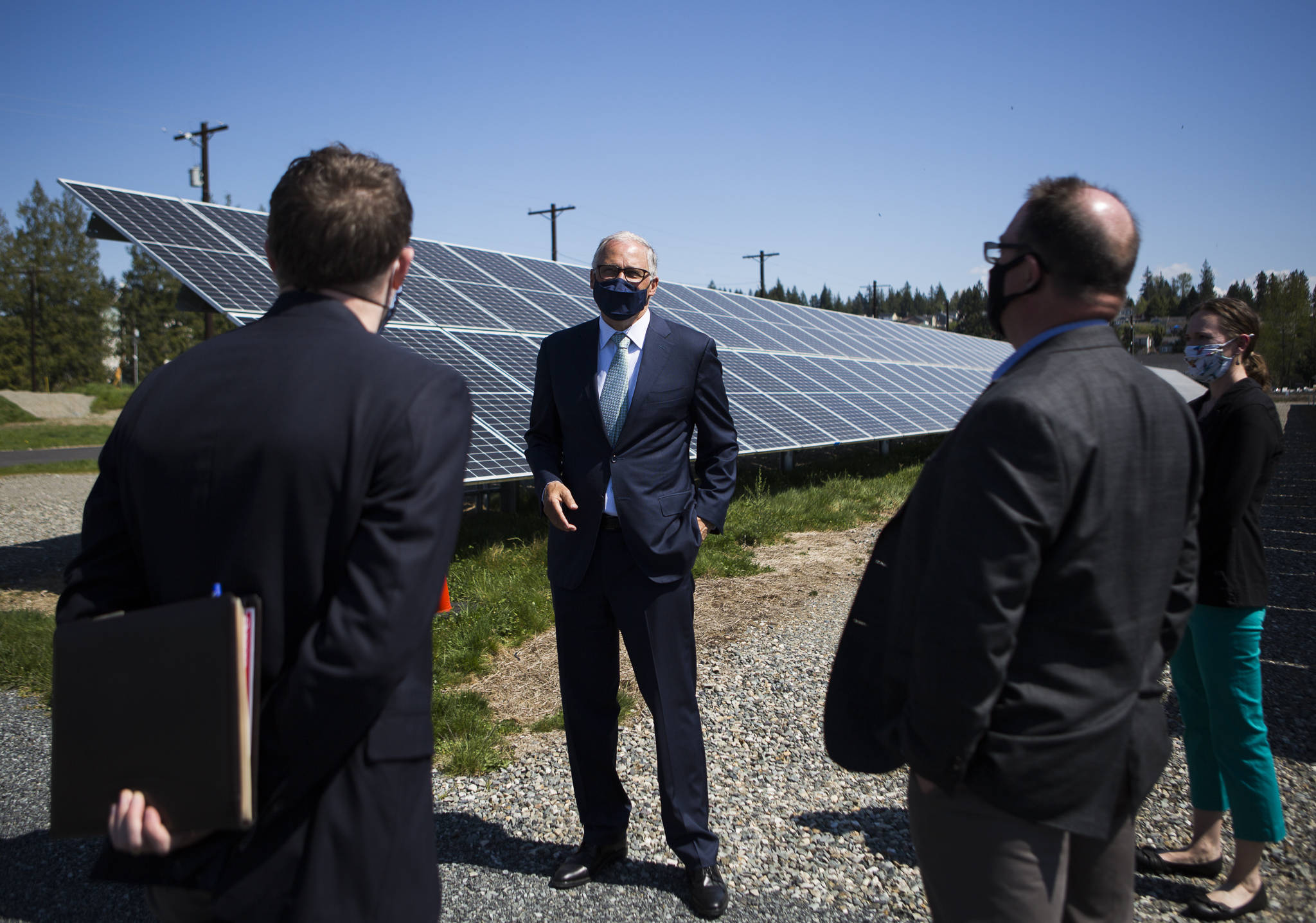 Gov. Jay Inslee stands in front of a line of solar panels that are a part of County PUD's microgrid. (Olivia Vanni / The Herald)