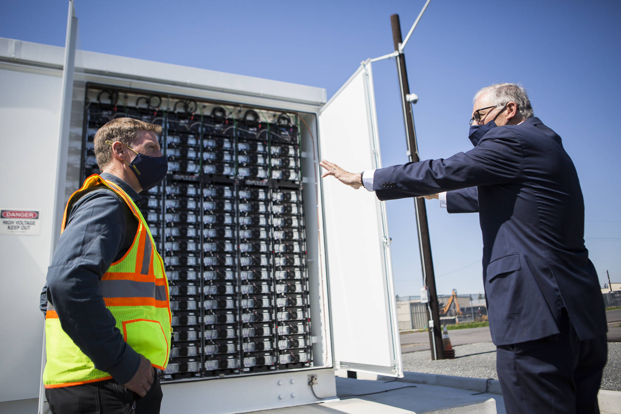 Gov. Jay Inslee (right) speaks to principal engineer Scott Gibson about the microgrid batteries. (Olivia Vanni / The Herald)