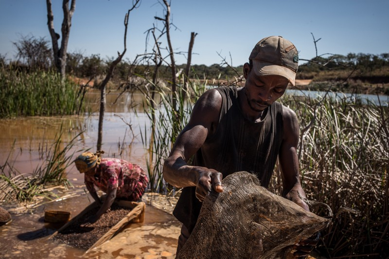A woman and a man separating cobalt from mud and rocks by a river in the Democratic Republic of Congo
