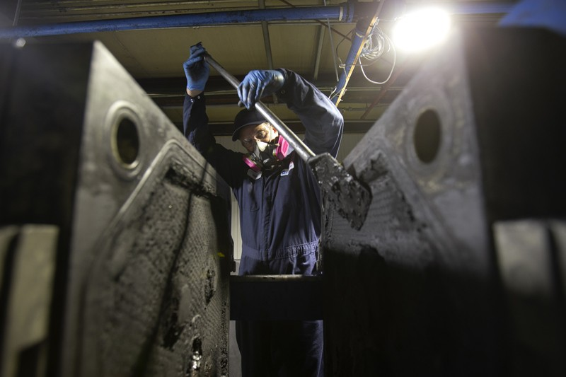 A worker scrapes black mass off metal plates at the Li-Cycle lithium-ion battery recycling facility